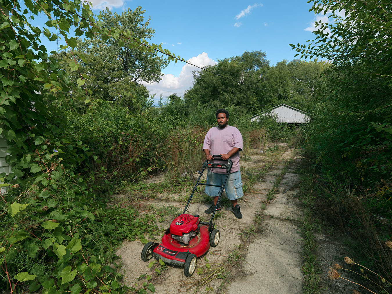 Leonard Mowing Overgrowth in Abandoned Lot, Delray, Detroit 2012